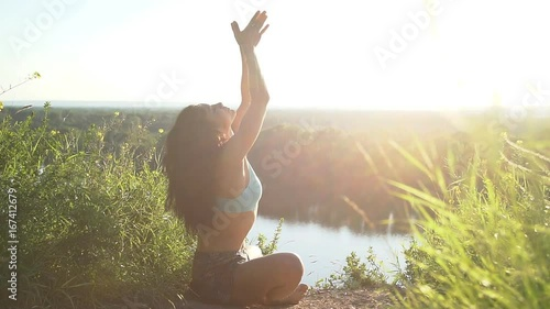 Wall mural Happy young woman practicing yoga at sunset. Healthy active lifestyle concept. Slow Motion