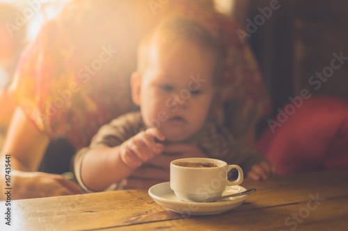 Wall mural Baby reaching for cup of coffee