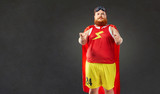 A fat funny man in a superhero costume points a hand at you - 167445831