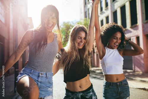Three beautiful girls walking around the city and having fun