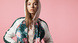 Fashionable beautiful young woman in a bomb jacket with floral print stands on a pink background - 167448279