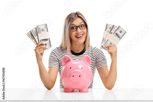 Cheerful woman behind a table with bundles of money and a piggybank isolated on white background - 167456888