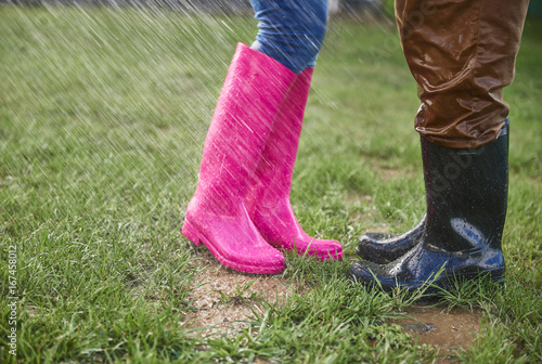 Man and woman in rubber boots outdoors in rainy day Poster