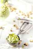 Pistachio ice cream with crushed nuts on the white wooden background - 167483623