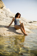Quadro Pretty yung woman on the stony seaside beach