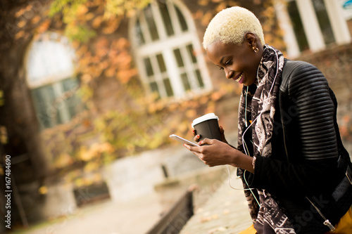 Wall mural Young black woman with coffee cup and mobile phone on the street