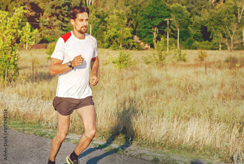 A handsome bearded man is engaged in jogging. Running along the asphalt outside the city. Healthy lifestyle. Running through the sunset. Toned
