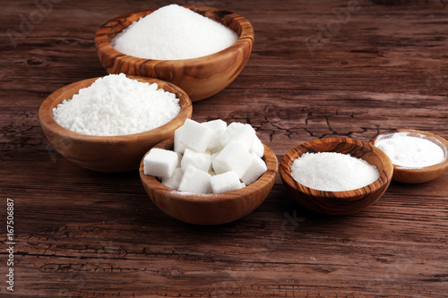 Sugar composition with white sugar in bowls on wooden board