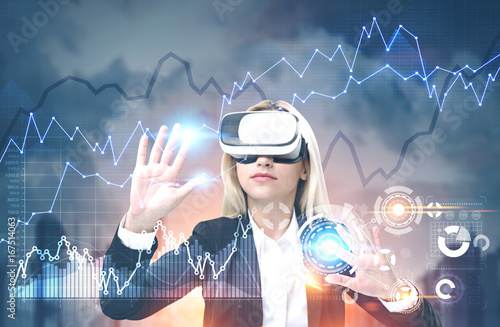 Woman in VR glasses, graphs, HUD and a city - 167514063