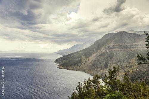 Tuinposter Grijs Dark stormy sky, sea waves, mountains.