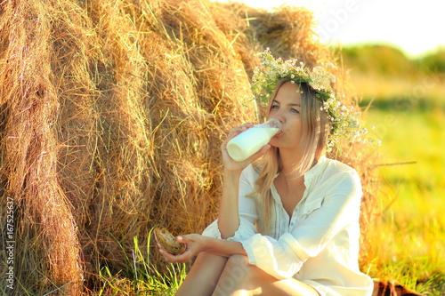 Foto op Plexiglas Milkshake девушка у стога сена пьет молоко из бутылки