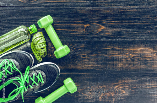 Sneakers dumbbells and a bottle of water. Flat view. All in one color.