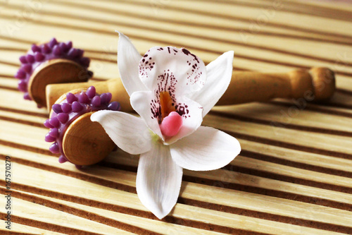 Staande foto Spa Orchid and a device for massage on a wooden background