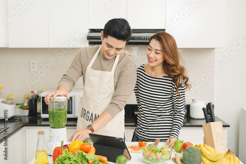 Sticker Portrait of happy asian young couple cooking together in the kitchen at home.