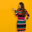 Surprised Young Woman In Colorful Striped Dress Is Presenting