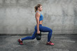 The girl makes lunges with kettlebells