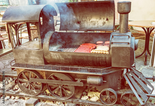 Barbecue grill with meat in shape of old steam locomotive, yellow filter Poster