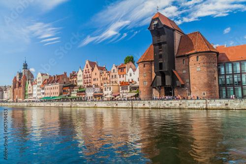 obraz PCV GDANSK, POLAND - SEPTEMBER 2, 2016: Riverside houses by Motlawa river in Gdansk, Poland. Medieval crane in the background.