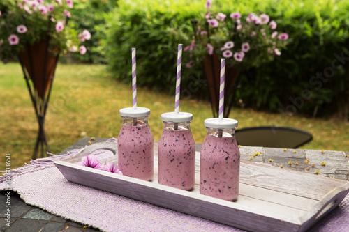 Foto op Plexiglas Milkshake Drei Gläser Heidelbeershake mit Strohalmen im Garten