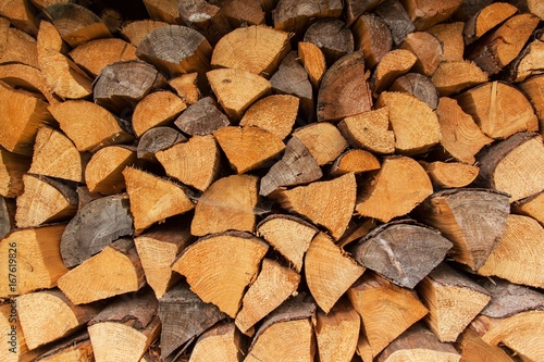 Timber stock for winter. Dry logs of wood in the background. Sale of wood.