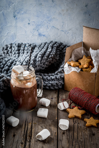 Foto op Canvas Chocolade Traditional autumn winter drinks and treats. Cup of hot chocolate with marshmallow and ginger biscuit stars, in gift box, old rustic wooden table. Cozy atmosphere, copy space