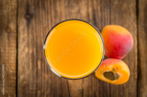 Portion of Apricot Juice on wooden background (selective focus)