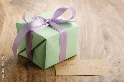 green gift box with purple bow wood background with valentines day greeting card