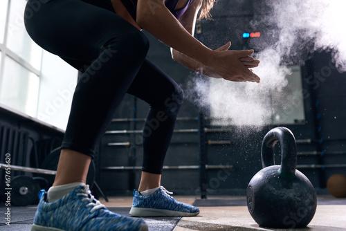Młoda kobieta podnoszenia Kettlebells w CrossFit Gym