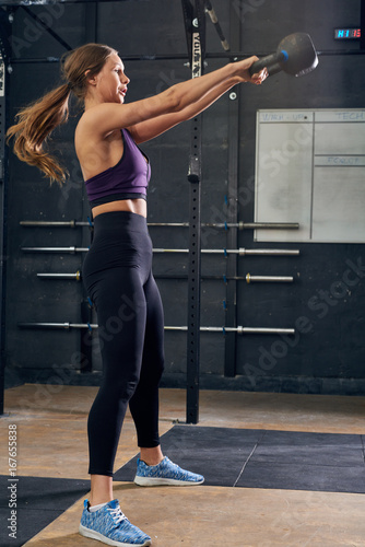 Sticker Young Woman Swinging Kettlebell in CrossFit Gym