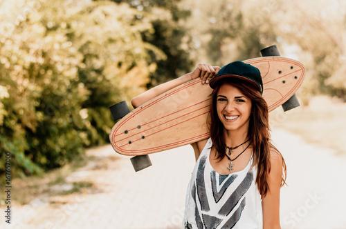 Foto op Aluminium Skateboard Attractive skater girl holding skateboard in her hands