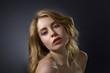 Attractive blonde woman on dark background .