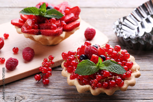 Dessert tartlets with berries on grey wooden table