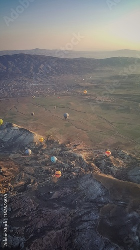 Sun is rising over the mountain. Scenic aerial view of hot air ballons