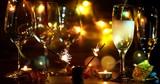 festlicher Anlass / Sekt wird in zwei Gläser eingeschenkt während Wunderkerzen brennen, im Hintergrund ein schönes Bokeh - 167689240