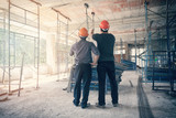 Engineer discussing with foreman about project in building construction site - 167696250