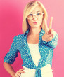 Quadro Young woman giving the peace sign on a pink background