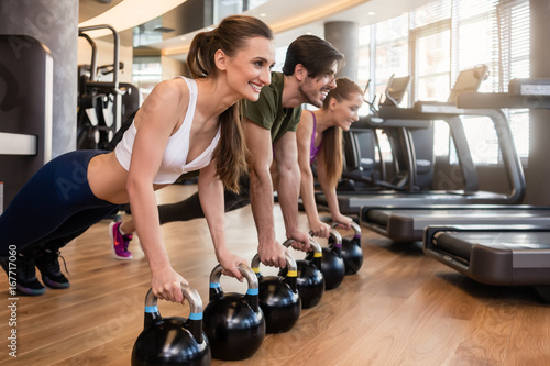 Poster Side view of three young people smiling while doing the kettlebell plank challenge for strong core during group workout at the gym