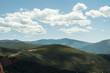 Paisaje montañoso cubierto de vegetación bajo un cielo azul con nubes.