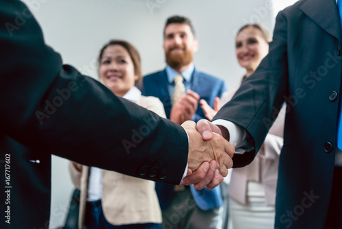 Close-up on handshake of two business men in applauses of three employees, after an important agreement for the success of the company - 167717602