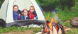 Children's tourism. Happy kids  girls in campaign in tent near fire