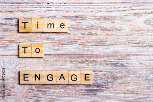 time to engage text on cubes on wooden background Poster