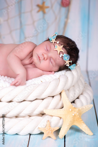 Close portrait of a sleeping newborn girl in the maritime hoop of starfish and p Poster