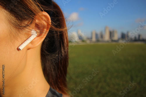 Fototapeta Mixed race fitness woman in park with city skyline in background with airpods close up