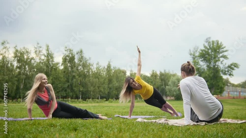 Sticker Yoga in park - Coach teaches two attractive girls