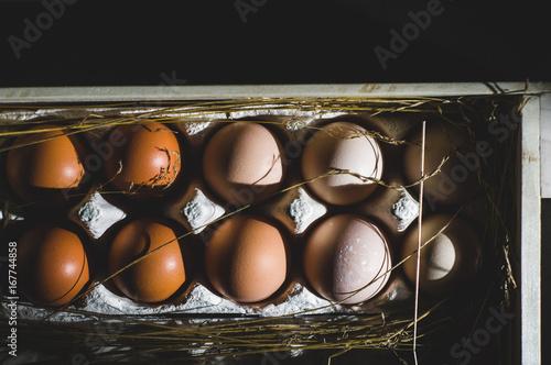 Chicken eggs in a wooden box. Dark style shot