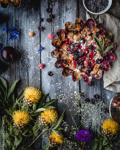 Wall mural assorted berry pie in a metal baking form with textile, yellow and purple flowers,small plate with dried lavender, plums, plate with a slice of pie and spoon on a gray wooden background, top view