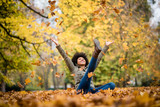 Autumn woman sitting with arms raised - 167746425