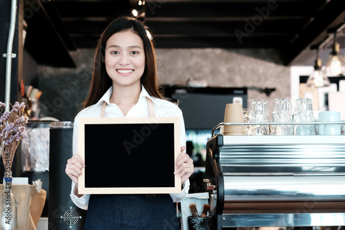 Sticker Young asian women Barista holding blank chalkboard menu with smiling face at cafe counter background, small business owner, food and drink industry concept