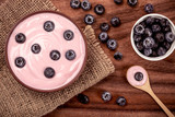 close up   pink creamy homemade blueberries fruit yogurt with fresh green mint leaf on wooden table background