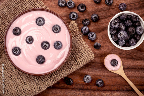 close up   pink creamy homemade blueberries fruit yogurt with fresh green mint leaf on wooden table background - 167755237